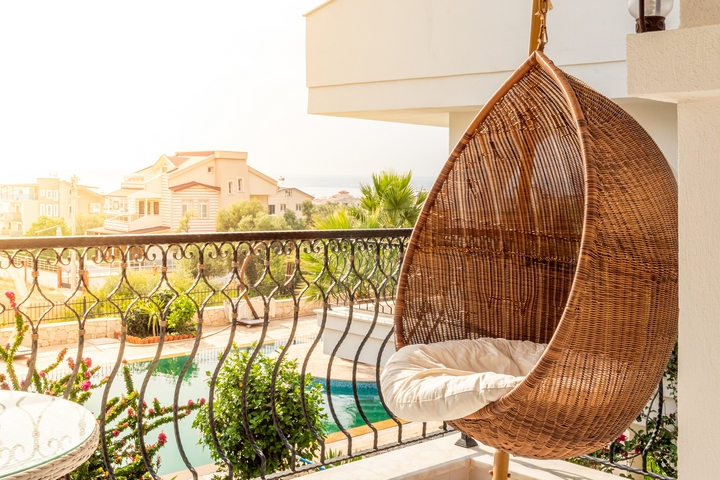 A swing seat can be a great idea for the condo balcony design.